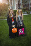 Little kids going trick or treating on Halloween in their costumes. Two cute little girls dressed in Halloween costumes going trick or treating outdoors in Stock Image