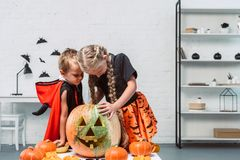 little kids in halloween costumes looking into pumpkin royalty free stock images