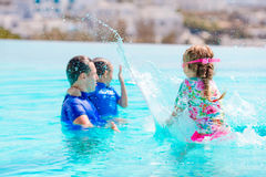Little kids and happy father having fun in outdoors swimming pool. Happy family having fun together in outdoors swimming pool Stock Photos