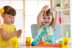 Little kids having fun together with colorful modeling clay at daycare. Creative kids molding at home. Children girls Stock Photo
