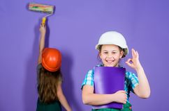 Little kids in helmet with tablet and roller. engineering idea. Future career. Painting wall. Foreman inspector. Labor stock photos