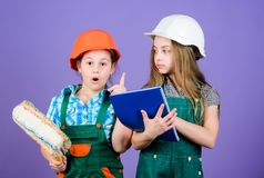 Little kids in helmet with tablet and roller. Labor day. 1 may. small girls repairing together in workshop. Foreman royalty free stock photography