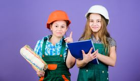 Little kids in helmet with tablet and roller. small girls repairing together in workshop. engineering idea. Labor day. 1 stock images