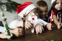 Little kids holding Christmas character decorated popsicle sticks royalty free stock photos