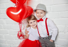 Little kids holding and picking up heart balloons. Valentine's Day and love concept, on white background Royalty Free Stock Photo