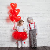 Little kids holding and picking up heart balloons. Valentine's Day and love concept, on white background Stock Photo