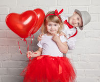 Little kids holding and picking up heart balloons. Valentine's Day and love concept, on white background Royalty Free Stock Photography