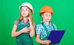 Free Little Kids In Helmet With Tablet. Labor Day. 1 May. Small Girls Repairing Together In Workshop. Foreman Inspector Royalty Free Stock Photos - 168169158