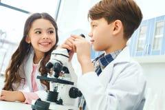 Little kids learning chemistry in school laboratory communication