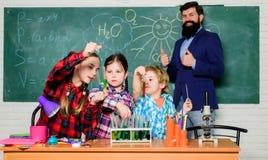 Little kids learning chemistry in school laboratory. school kids scientist studying science. happy children teacher stock image