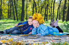 Little kids lying close together in an autumn park Stock Photo
