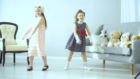 The little kids made a disco. Two beautiful little girls dancing. The children had a disco. The concept of fun and relaxation. There are Teddy bears on the couch stock video footage