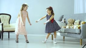The little kids made a disco. Two beautiful little girls dancing. The children had a disco. The concept of fun and relaxation. There are Teddy bears on the couch stock video