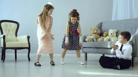 The little kids made a disco. Two beautifully dressed girls dancing and sitting next to a boy and applauds. The children had a disco. The concept of fun and stock footage