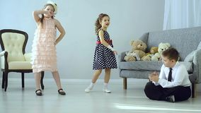 The little kids made a disco. Two beautifully dressed girls dancing and sitting next to a boy and applauds. The children had a disco. The concept of fun and stock video