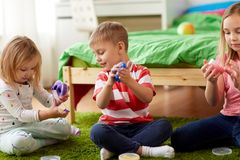 Little kids with modelling clay or slimes at home. Childhood, leisure and people concept - little kids with modelling clay or slimes at home Stock Images