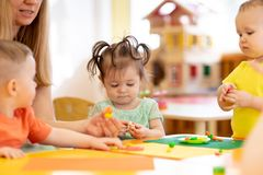 Little kids molded from clay toys. Teacher plays ith children. stock photos