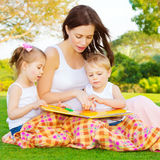 Little kids with mommy read book. Image of cute young female with two little children read book outdoors, brother and sister with mother learning in the park in Stock Images