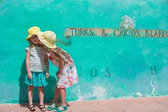 Little kids near big map of Caribbean island Turks Royalty Free Stock Images