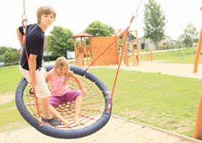 Little kids on a net swing. Hairy little girl sitting and boy standing and swinging on a net swing made from ropes with kids playground behind Stock Image