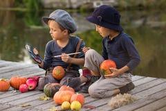 Little kids paint small Halloween pumpkins Stock Photo
