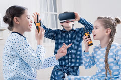 Little kids in pajamas playing with walkie-talkies and virtual reality headset royalty free stock image