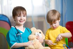 Little kids play doctor with plush toy Royalty Free Stock Images