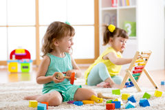 Little kids playing with abacus and constructor toys in kindergarten, playschool or daycare center royalty free stock images
