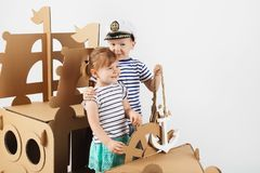 Little kids playing with cardboard ship on white background. Hap. Py children. Childhood. Fantasy, imagination royalty free stock photos