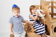 Little kids playing with cardboard ship on white background. Hap. Py children. Childhood. Fantasy, imagination Royalty Free Stock Images