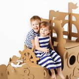 Little kids playing with cardboard ship on white background. Hap royalty free stock photography