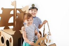 Little kids playing with cardboard ship on white background. Hap. Py children. Childhood. Fantasy, imagination Royalty Free Stock Image