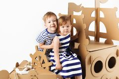 Little kids playing with cardboard ship on white background. Hap. Py children. Childhood. Fantasy, imagination royalty free stock photography