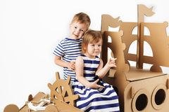 Little kids playing with cardboard ship on white background. Hap. Py children. Childhood. Fantasy, imagination stock images
