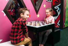 Little kids playing chess in entertainment center Stock Images
