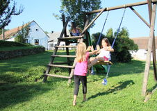 Little kids - girls playing on swing. Barefoot little kids - girl in white t-shirt and pink shorts swinging on a swing while playing with second girl standing in Stock Photos