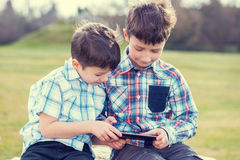 Little kids playing on tablet outdoor vintage Royalty Free Stock Photography