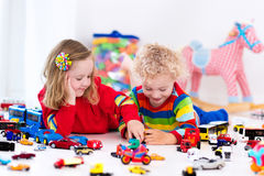 Little kids playing with toy cars Stock Photos