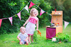 Little kids playing with toy kitchen in the garden. Funny curly little girl and adorable baby boy, cute brother and sister, playing together with a vintage Royalty Free Stock Images