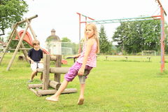 Little kids playing on wooden swing. Little girl and boy - kids playing and swinging on wooden swing on kids playground Stock Images