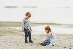 Little kids portrait. Two little kids playing outdoors by the lake, wearing grey clothes royalty free stock photo