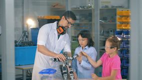 Little kids and a research specialist are moving robot`s limbs. 4K