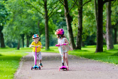 Little kids riding colorful scooters Royalty Free Stock Photo