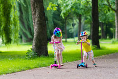 Little kids riding colorful scooters. Children learn to ride scooter in a park on sunny summer day. Preschooler boy and girl in safety helmet riding a roller stock images