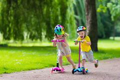 Little kids riding colorful scooters Royalty Free Stock Images
