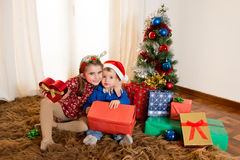 Little kids on rug opening Christmas Presents Stock Images