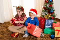 Little kids on rug opening Christmas Presents. Cute little kids on rug opening Christmas Presents Royalty Free Stock Photography