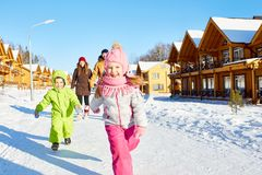 Children enjoying winter walk. Little kids running outdoors on sunny winter day and smiling at camera happily while their parents walking behind Royalty Free Stock Image