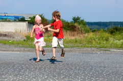 Little kids running in street Stock Images