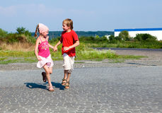 Little kids running in street Stock Photography